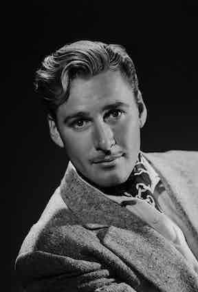 Errol Flynn wearing a chain printed silk cravat beneath a textured boucle jacket, circa 1937.