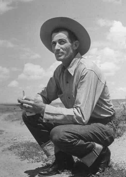 Wearing the cowboy's uniform of selvedge denim jeans and a sturdy cotton shirt complete with cigarettes in hand, circa 1950s.