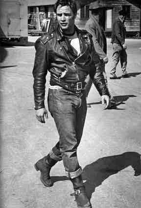 The look that changed it all. Marlon Brando on the set of The Wild One in 1953, wearing his iconic outfit consisting of a black leather Schott Perfecto motorcycle jacket and turn-up denim jeans.