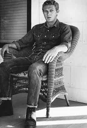 Steve McQueen was a big wearer of denim. On this occasion he opted for a Western shirt combined with jeans and rugged work boots, circa 1960s.