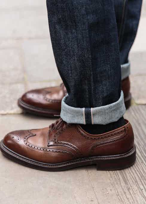 A pair of jeans can be dressed up easily by a sharp pair of brogues. Here, Blackhorse Lane's E5 jeans are worn with a pair of Crockett & Jones shoes.