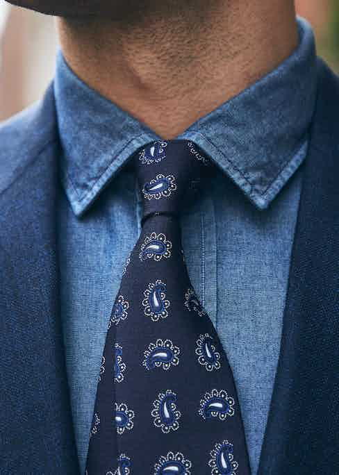 A denim shirt can break up the formality of a suit. Here is Salvatore Piccolo's example, paired with a printed silk tie and indigo suit jacket.