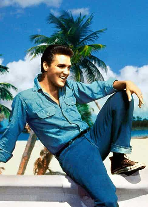 Elvis Presley wearing double denim with high-top canvas sneakers, circa 1950s.