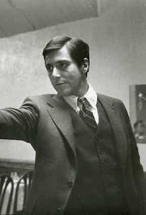 Michael Corleone, gun aloft, sporting a grey flannel three-piece suit with a striped tie and Oxford cotton button-down shirt in the famous restaurant scene.