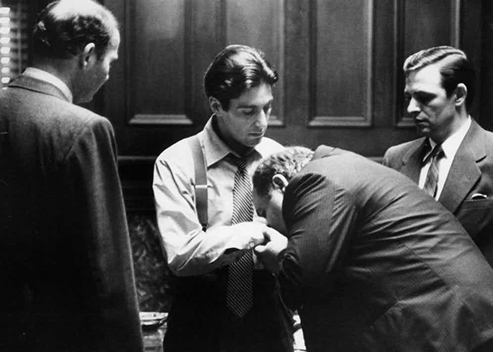 The closing scene shows Michael Corleone wearing shirtsleeves in a white business shirt with a loosened black-and-silver striped, smooth silk tie.