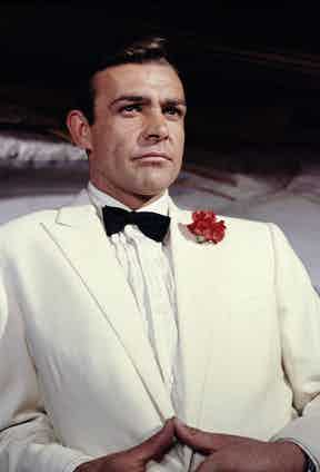 Connery's Bond wears a white dinner jacket with a pleated evening shirt, bow tie and flower in the lapel in Goldfinger, 1964.