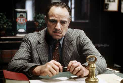 Don Vito Corleone sporting a rustic tweed single-breasted suit with a light blue shirt and red printed tie.