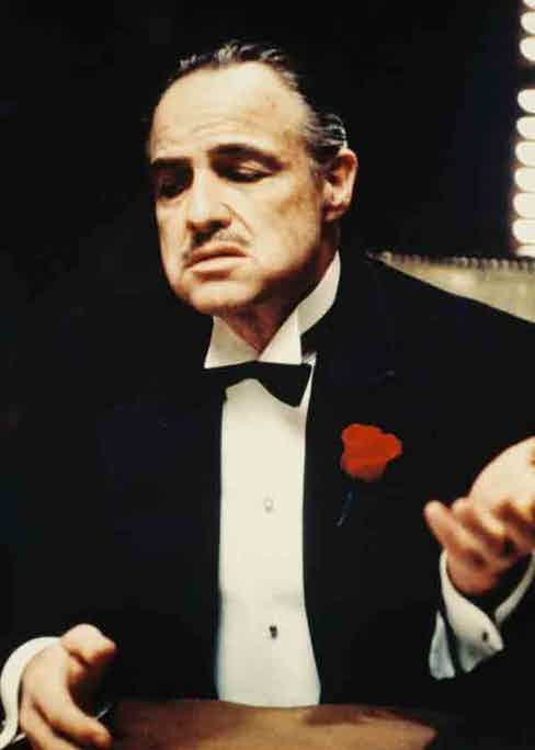 Marlon Brando as Don Vito Corleone wearing a black three-piece dinner suit with silk notched lapels, a white dress shirt, black bow tie and a red floral boutonniere.