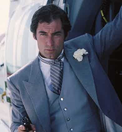 Timothy Dalton in Licence To Kill, wearing a grey striped dress cravat and large boutonniere, 1989.