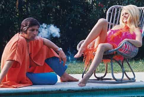 Gunther Sachs and Brigitte Bardot laze by the pool, circa 1967.