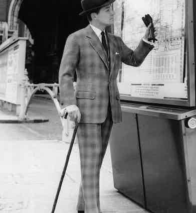 A finely dressed gentleman checks the train timetable wearing a suit cut in oversized checked cloth.