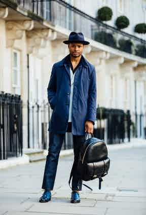 Black leather injects a sense of formality into this gentleman's backpack, worn with a double-breasted jacket and macintosh, double-monk shoes and a fedora. Photo by Jamie Ferguson.