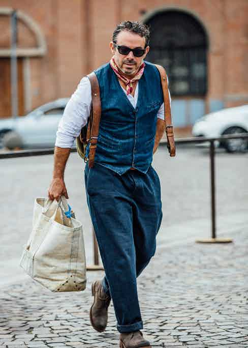 The vintage feel of a collarless shirt, denim waistcoat and pleated turn-ups is underlined by a well-worn canvas backpack with leather accents. Photo by Jamie Ferguson.