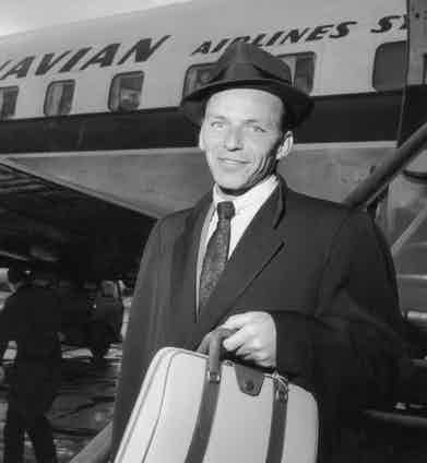 Frank Sinatra arrives in London, briefcase in hand, in 1956.