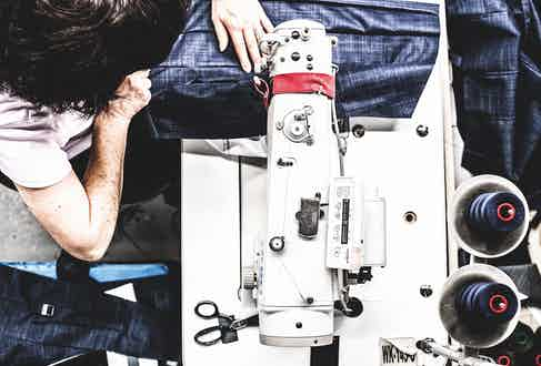 A worker machine-stitching together a parka coat.