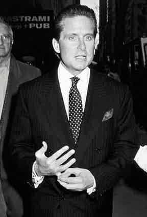 Wearing a double-breasted pinstriped suit over a horizontally-striped shirt, spotted tie and pocket square, Gekko holds his signet ring in a traditional power stance. Photograph by Ron Galella/WireImage.