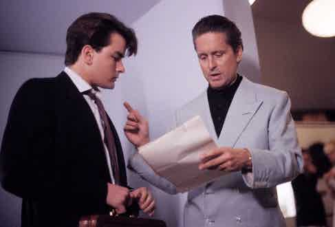 When opting for a more casual look, Gekko wears a light blue 4x2 double-breasted linen jacket with clear buttons over a black polo shirt. Pictured here with Bud Fox played by Charlie Sheen, 1987.