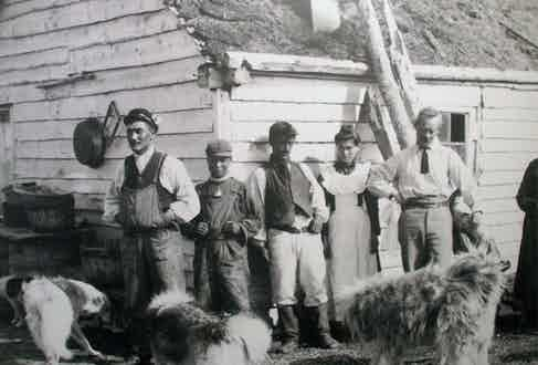 Sir Wilfred Grenfell poses with local fisherman on the Labrador coast, a few of which are wearing overalls made from Grenfell Cloth, circa 1935.