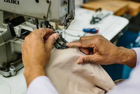 A craftsman sewing on a button which then gets scrupulously checked by Rima, Grenfell's quality control officer. Photo by Jamie Ferguson.