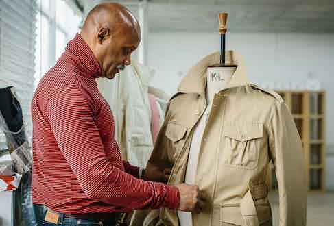 Joslyn Clarke, Creative Director at Grenfell, works on a sample belted safari jacket.  Photo by Jamie Ferguson.