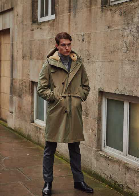 The concealed belt acts as a mediator between the trench coat's buckled belt and the parka's drawstring waist.