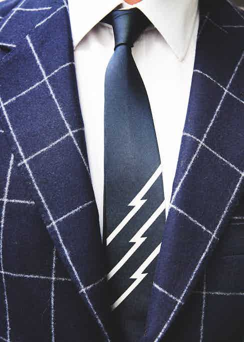 This suit and tie combination gleefully links heritage and modernity. The suit is a chalkstripe navy suit from legendary Italian tailor Caraceni, demonstrating exquisite taste when looking beyond Savile Row. The tie is a well paired Uniform Experiment in collaboration with Fragment Design's Hiroshi Fujiwara.