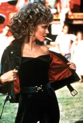 Olivia Newton-John's Sandy from 1978's Grease sports a black leather jacket with a red lining and belted waist.