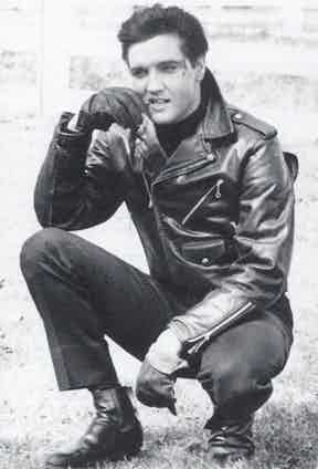 Elvis Presley wears a black leather jacket with a doubled-over front and generous collar which he turns up, paired with driving gloves, leather Chelsea boots and a black sweatshirt in Roustabout, 1964.