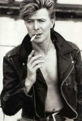 David Bowie dons a leather motorcycle jacket in true rock star style, worn open with no shirt underneath and a cigarette casually hanging from his mouth, circa 1987.