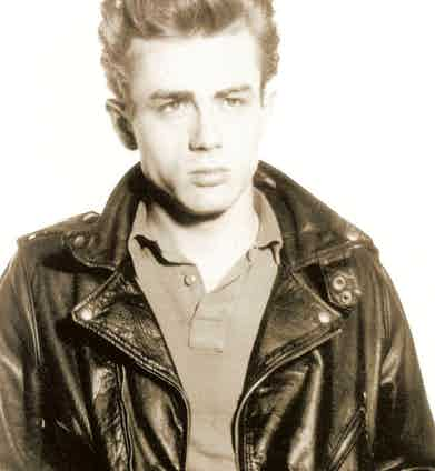 James Dean favoured leather jackets as part of his off-duty attire, pictured here wearing a black version over a polo shirt, circa 1954.
