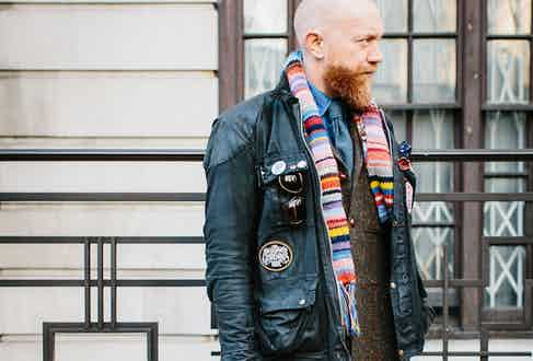 Dean Gomilsek-Cole, Turnbull & Asser's Head of Design & Product Development, dons a vintage wax motorcycle jacket adorned with metal and sewn badges over a tweed Siren Suit, blue denim shirt, tie and hand-knitted scarf. Photograph by Jamie Ferguson.