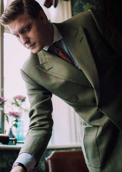 Tom is a loyal patron of Kent, Haste & Lachter, having been introduced to the tailoring house by menswear expert Nick Foulkes. His double-breasted sports coat is cut in an olive green Bateman Ogden tweed with an overcheck that, at first sight, appears red, but on closer inspection has lovely flecks of pink, orange and gold woven through. The inverted box pleat pockets and a half-belt in the back are personal touches Tom requested.