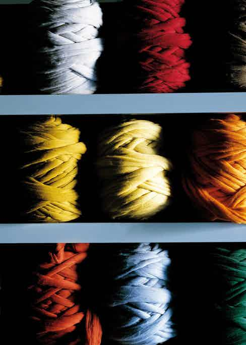 Dyed bobbins of yarn ready to be applied to the warping beam. Photograph by Luke Carby.