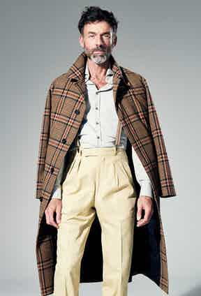 Brown and black wool Prince-of-Wales coat, AMI; pale grey cotton shirt, Thom Sweeney; cream cotton trousers, Anderson & Sheppard Haberdashery; camel and brown polyester, elastane and leather braces, Albert Thurston at The Rake. Styling by Jo Grzeszczuk, photograph by Jake Walters.