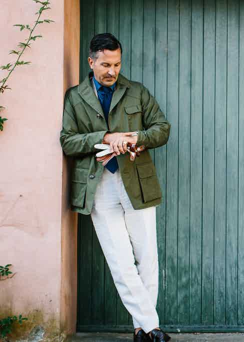Alexander Kraft in a khaki green cotton field jacket with patch pockets, layered over a denim shirt and blue tie, white tailored trousers and black leather loafers. Photograph by Jamie Ferguson.