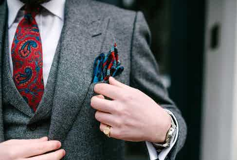 Bringing a pop of colour to a grey three-piece suit with an Augustus Hare red paisley print tie and pocket square.