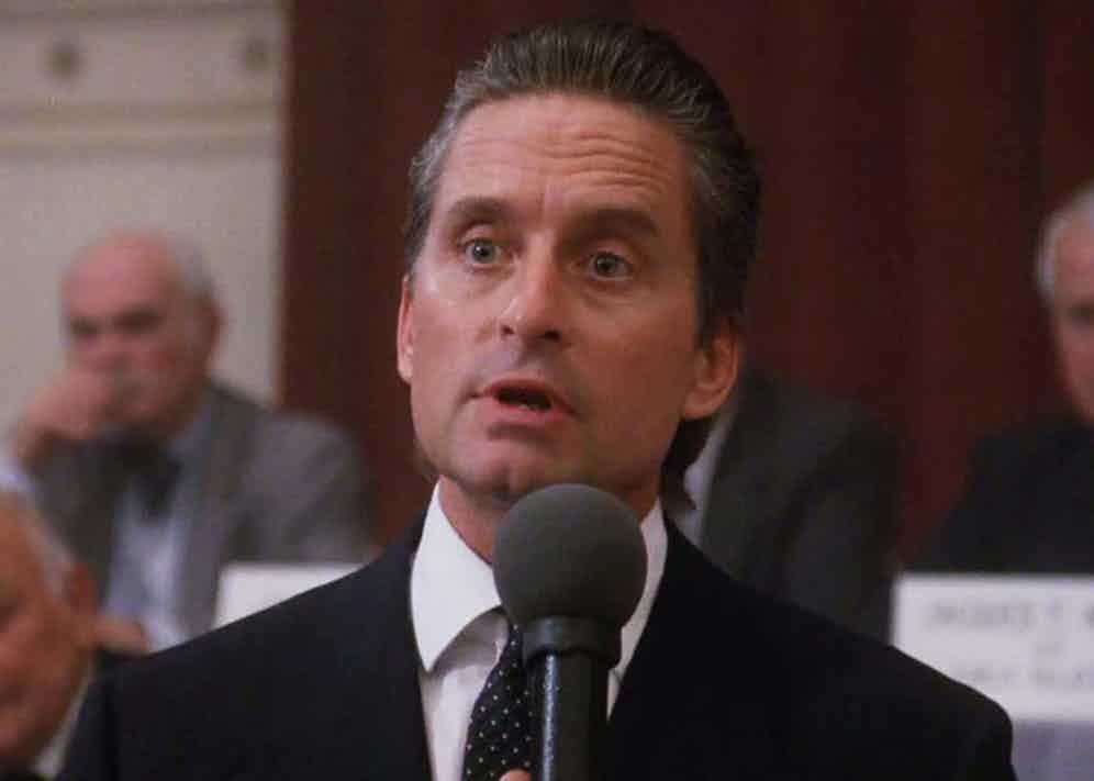 """During his iconic """"greed is good"""" speech, Gekko wears a grey double-breasted suit with a white double cuff shirt and spotted tie, finished with a simple white pocket square."""