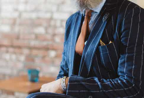 """The grenadine silk tie in bronze is from Aklasu, an Italian brand. """"Their workmanship is superb, and this is completely hand-made."""" His bright yellow silk pocket square is vintage."""
