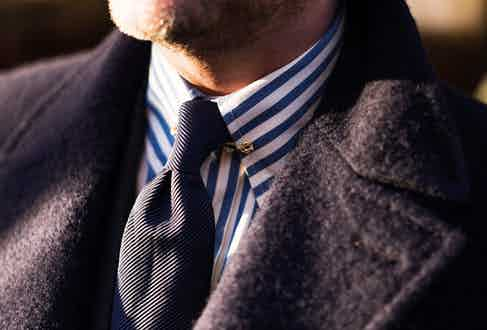 A ribbed tie adds texture and results in the formation of a small pleat beneath the knot and is further lifted by a gold collar pin. Photograph by Luke Carby.