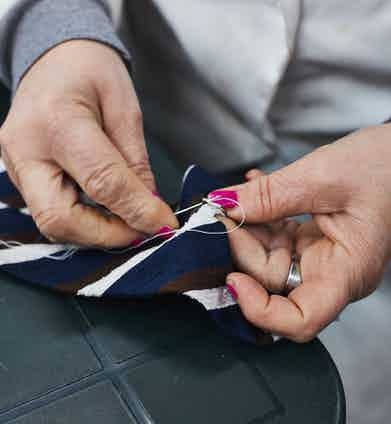A label is hand-sewn onto a Francesco Marino tie at its factory in Naples, Italy. Photograph by James Munro.
