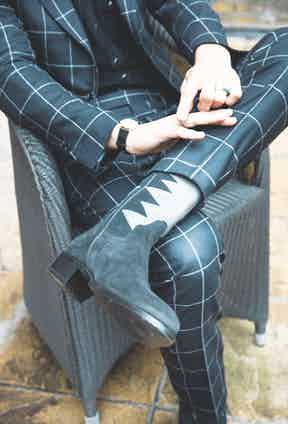 The Cormac cowboy boots are,  naturally, by Barbanera, while the suit  is made by a Roman tailor, Sartoria  Giuliva, in a windowpane check by VBC.