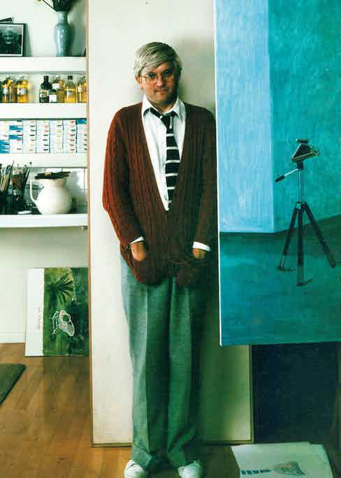 David Hockney, master of the casual tie, pairs a large striped tie with an open shirt collar and knitted cardigan as he poses next to his work in London, 1978.
