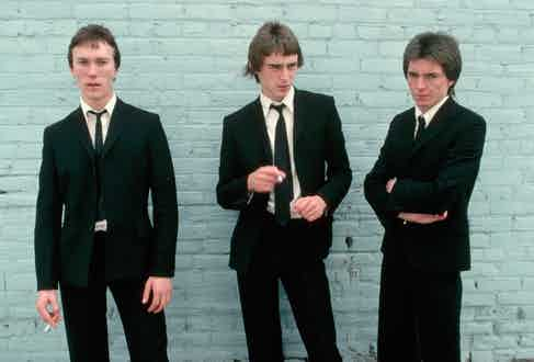 English punk rock band The Jam pose in matching black suits with their slim black ties left slightly undone for their album cover, 1977.
