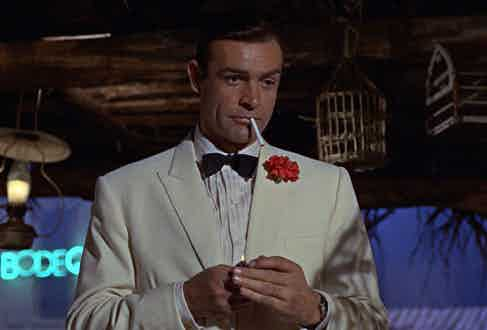 Connery sports a cream dinner jacket, pleat-front shirt and bow tie.