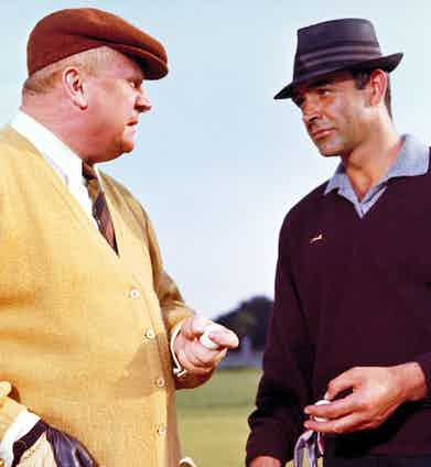 James Bond, wearing a Slazenger V-Neck, goes head-to-head with Goldfinger during a round of golf.