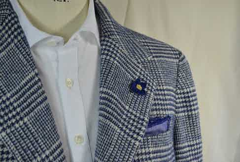 The navy and white houndstooth jacket with a knitted flower lapel pin layered over a crisp white shirt.