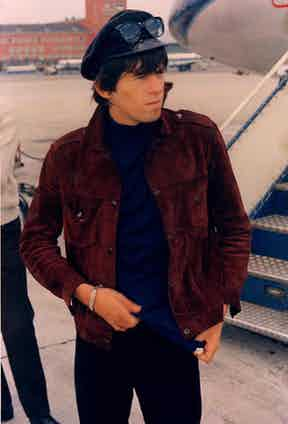 Richards boards a private jet donning a dark tan suede jacket, a navy roll neck and black jeans, topped with peaked cap and Ray Ban sunglasses, 1965.