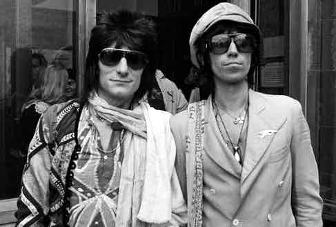 Wearing a whimsical ensemble including a double-breasted jacket, large sunglasses and a leather baker boy cap with fellow band member Ron Wood, 1976. Photograph by T FITZPATRICK/REX/Shutterstock.