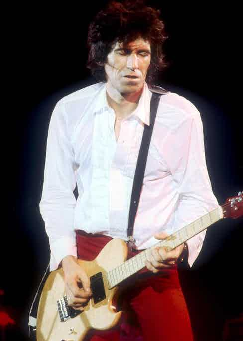 Richards pairs a white dress shirt with slim-fitting red trousers to perform while on tour in England, 1979. Photo by Andre Csillag/REX/Shutterstock.