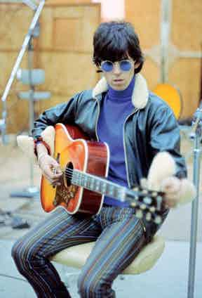 Wearing a shearling collar leather jacket with a violet roll neck and striped trousers while recording at RCA Studios in Hollywood, 1965.